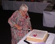 Joan Biscoe, the first chairman of the choir, cuts the cake.